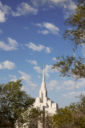 The top of the Ogden Utah Temple seen over the green leaves of the trees on the temple grounds, with a blue sky and clouds overhead.