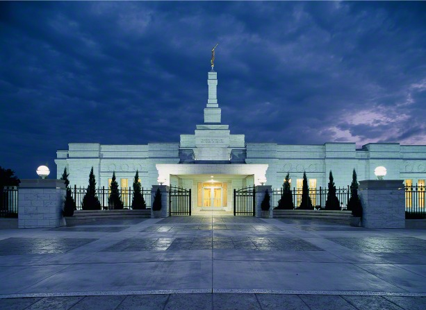 The Oklahoma City Oklahoma Temple entrance at night, with the lights on outside of the temple and warm light coming out from the windows and doors.