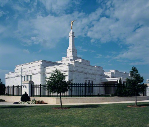 The Oklahoma City Oklahoma Temple on a sunny day, with a black fence around the perimeter of the grounds.