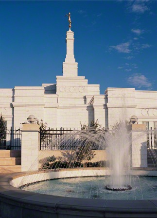 A water fountain on the grounds of the Oklahoma City Oklahoma Temple on a sunny day, with the temple seen on the left side and a blue sky overhead.