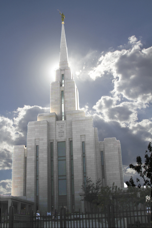 The front of the Oquirrh Mountain Utah Temple on a sunny day, with large white clouds and a ray of sun behind the temple's spire.