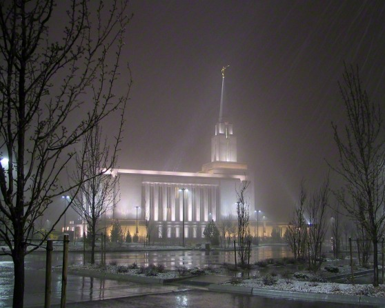 A side view of the Oquirrh Mountain Utah Temple on a snowy evening, with bare trees in the parking lot medians.