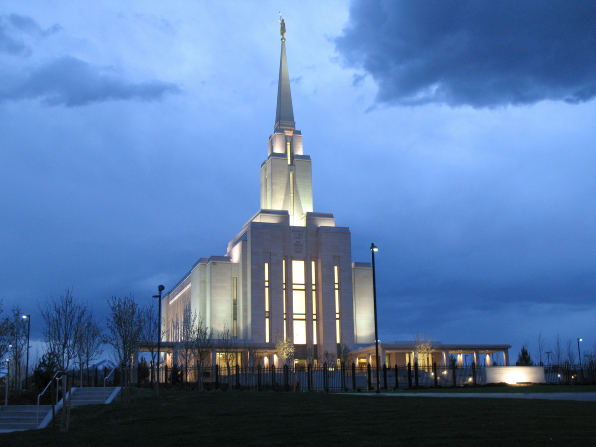 Oquirrh Mountain Utah Temple in the evening, with the lights on inside and outside, in front of a deep blue sky.