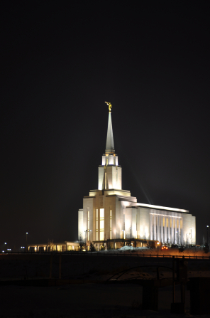 A front side view of the Oquirrh Mountain Utah Temple, with the lights on at night setting the temple apart from the black sky behind the temple.