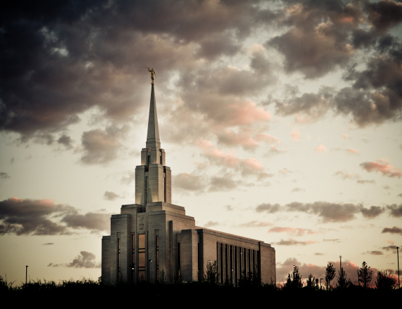 A front side view of the Oquirrh Mountain Utah Temple in the evening, with the temple's lights on and purple clouds overhead.