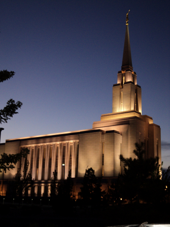 A side view of the Oquirrh Mountain Utah Temple in the evening, with the lights on and shadows of trees in the foreground.