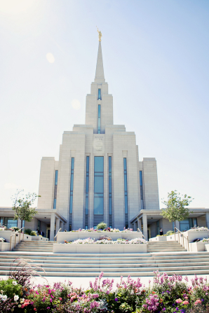 A front view of the Oquirrh Mountain Utah Temple on a spring day, with flowers and plants in the flower beds near the temple steps and door.