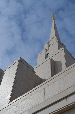 A view of the spire on the Oquirrh Mountain Utah Temple, looking toward the angel Moroni statue and the blue sky beyond.