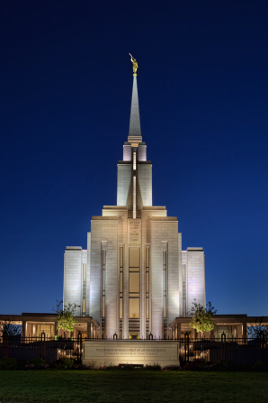 The front of the Oquirrh Mountain Utah Temple, with the lights on at night and a deep blue sky in the background.