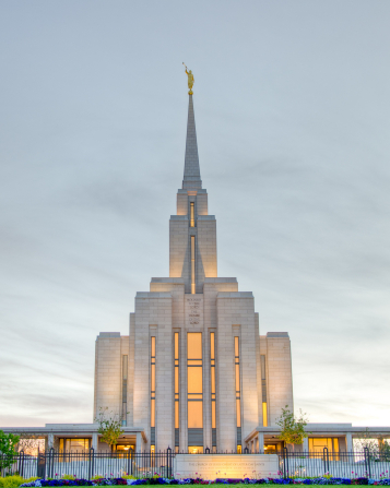 The front of the Oquirrh Mountain Utah Temple, with the lights on in the early evening and a row of colorful flowers on the grounds.