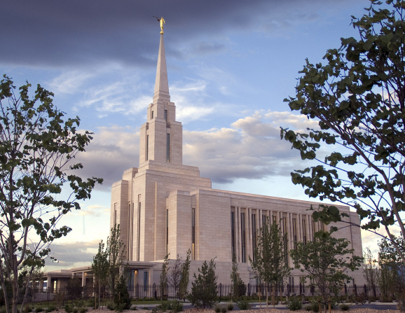 A side view of the Oquirrh Mountain Utah Temple, with small green trees in the foreground and other trees growing on the grounds near the temple.
