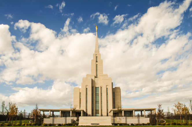 The front of the Oquirrh Mountain Utah Temple on a sunny day, with the temple sign and the black fence seen in the front and large white clouds overhead.
