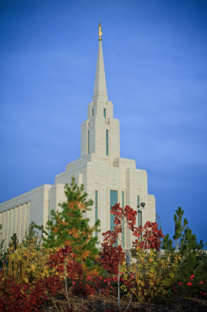 The Oquirrh Mountain Utah Temple on a sunny fall day, with autumn leaves on the trees in the foreground.