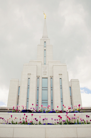 A front view of the Oquirrh Mountain Utah Temple on a spring day, with colored flowers in the front and a dull gray sky above.