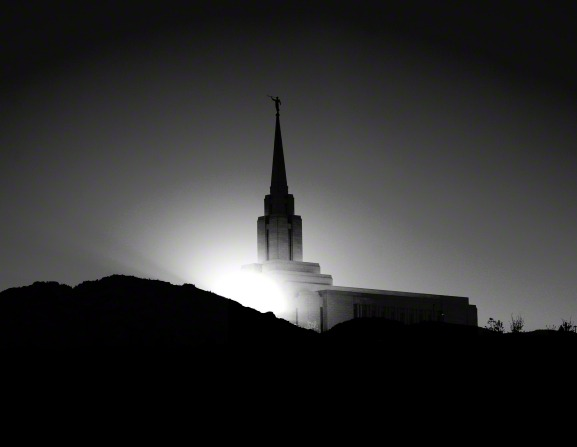 A black and white photograph of the Oquirrh Mountain Utah Temple's spire rising above a nearby hill.