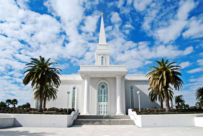 The front of the Orlando Florida Temple, with a vibrant blue sky and fluffy white clouds above and palm trees growing on either side of the temple.