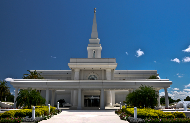 The front and entrance of the Orlando Florida Temple on a sunny day, with a nearly clear, vibrant blue sky overhead.