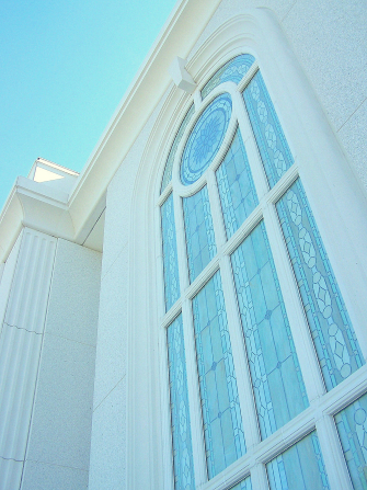A detail of a stained-glass window on the Orlando Florida Temple reflecting the blue light of the sky.