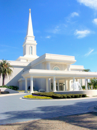 The front entrance to the Orlando Florida Temple on a sunny day, with a water fountain running near the door.