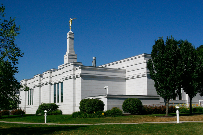 A view of the Palmyra New York Temple from one of the corners of the temple, with dark green trees in the foreground and a deep blue sky overhead.