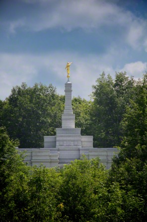 The spire and angel Moroni on the Palmyra New York Temple, seen over the green leaves of the trees on the grounds of the temple, with a blue sky above.