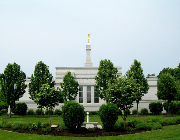 Leafy green trees on the grounds of the Palmyra New York Temple, partially obscuring a view of the temple with the angel Moroni on the spire.