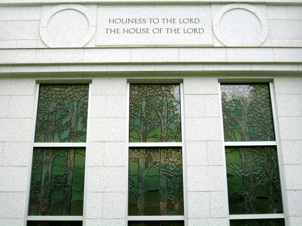 "Three stained-glass windows portraying the Sacred Grove on the Palmyra New York Temple, with ""Holiness to the Lord: The House of the Lord"" over them."
