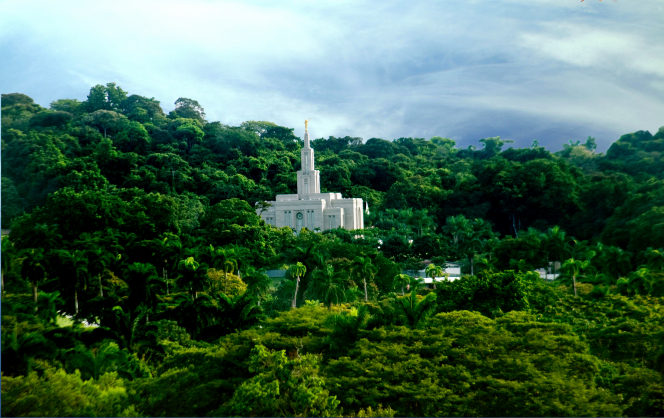 The Panama City Panama Temple seen in the distance amid many deep green trees.