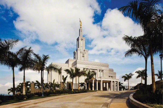 A road lined with palm trees leading up toward the Panama City Panama Temple, with a deep blue sky filled with white clouds.
