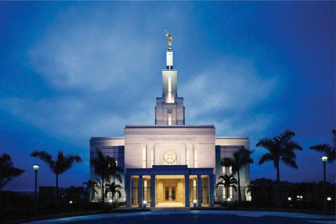 The front of the Panama City Panama Temple, with the lights on in the evening and palm trees growing on the path leading to the temple.