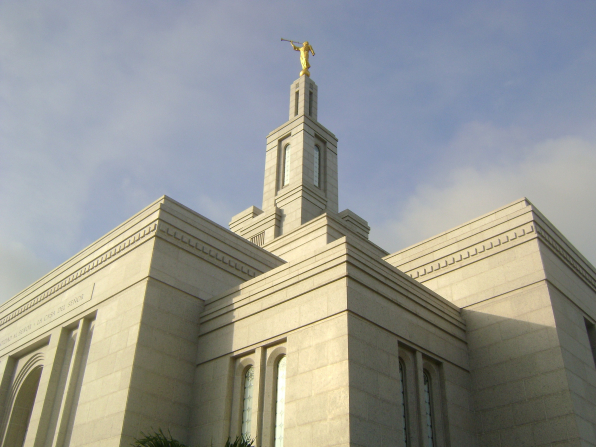 A view of the Panama City Panama Temple from below, looking up toward the spire, with a pale blue sky above.