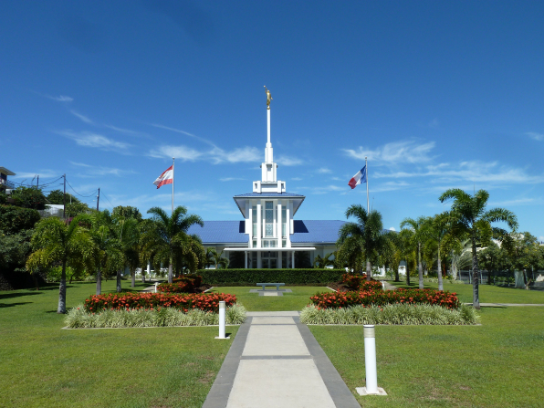 The Papeete Tahiti Temple and grounds on a sunny day, with the Tahitian and French flags flying outside the front of the building.