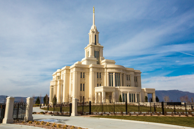 A view of the east side of the Payson Utah Temple during sunrise, including scenery and a clear sky.