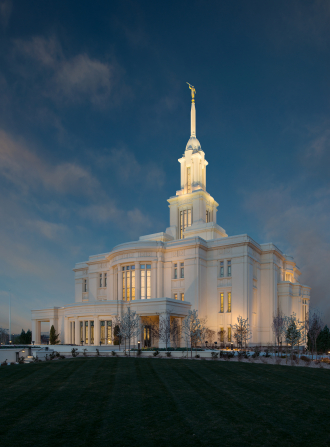 A view of the entire Payson Utah Temple in the evening, including scenery with a dark sky.