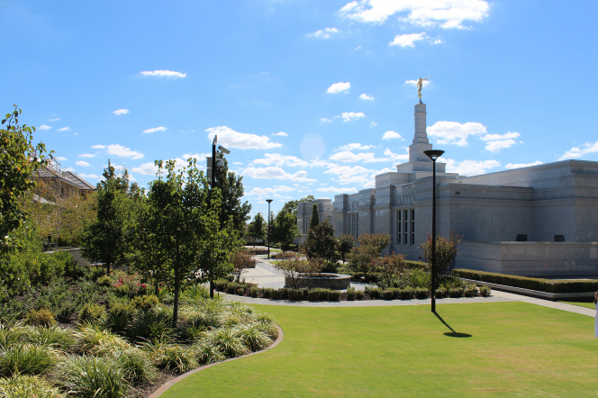 A view of the Perth Australia Temple from some distance back on the temple grounds, showing green trees growing to the left.