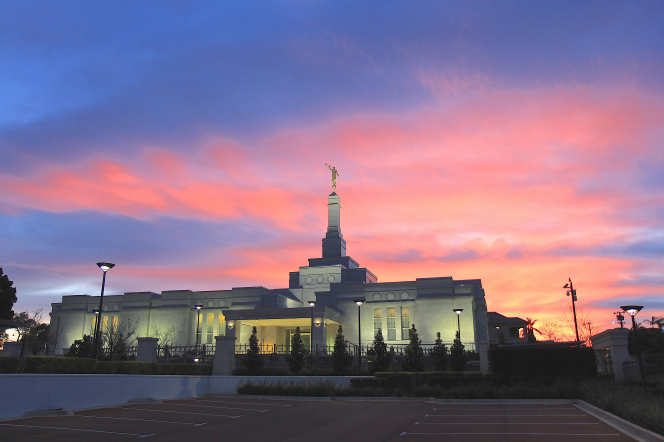 A yellow, pink, and purple sunset behind the illuminated Perth Australia Temple.