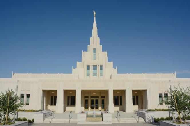A view of the Phoenix Arizona Temple entrance and spire during the day, including scenery.