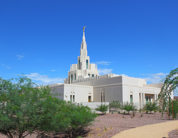 An angle view of the Phoenix Arizona Temple during the day, including scenery and a clear blue sky.