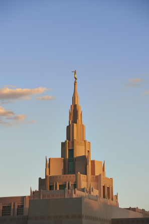 The Phoenix Arizona Temple during sunset with a few clouds in the sky.