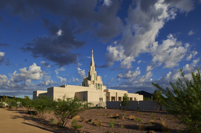 A side view of the Phoenix Arizona Temple at sunrise, with small gray and white clouds overhead and desert plants in the foreground.