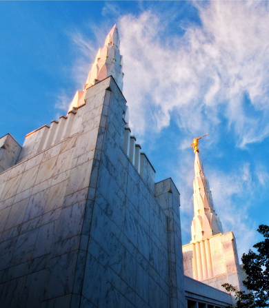 Two of the spires on the Portland Oregon Temple set against a blue sky, with the angel Moroni statue on top of the spire on the right.