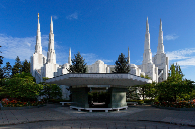 A side view of the Portland Oregon Temple showing all of the spires against a deep blue sky, surrounded by green trees.