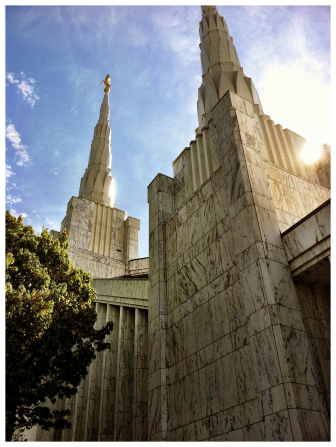 Some of the spires on the Portland Oregon Temple, with a ray of sun lighting up the right side and a green tree showing on the left.