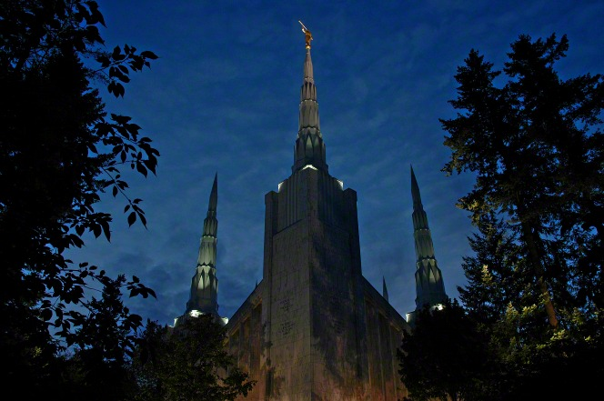 Several of the spires on the Portland Oregon Temple lit up in the evening, seen rising above the trees that grow near the temple.
