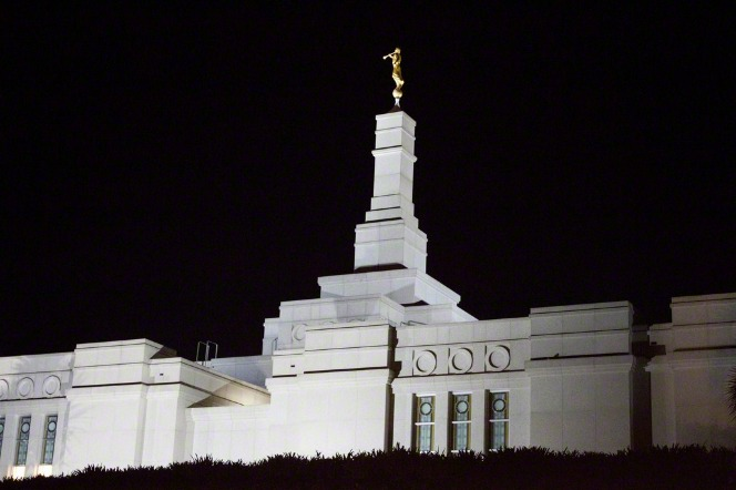 The spire and angel Moroni on top of the Porto Alegre Brazil Temple, lit up against a dark night sky.