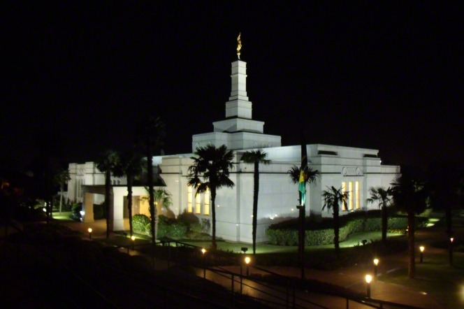 The entire Porto Alegre Brazil Temple with the lights on at night underneath a black sky.