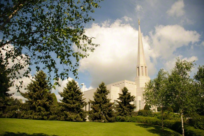 The spire of the Preston England Temple rising above the surrounding vegetation and trees on the temple grounds.