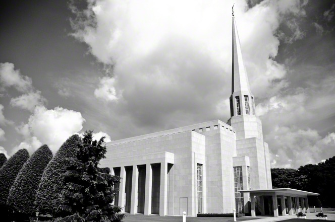 A side view of the Preston England Temple in black and white, with manicured bushes and trees growing on the grounds.