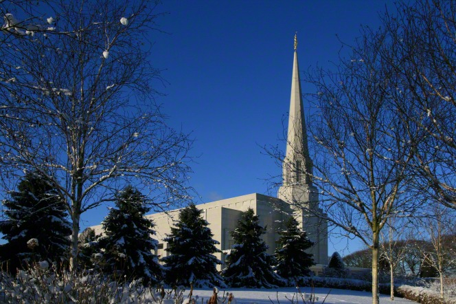 A side view of the Preston England Temple, seen between bare winter trees, over a snow-covered lawn, with a deep blue sky overhead.