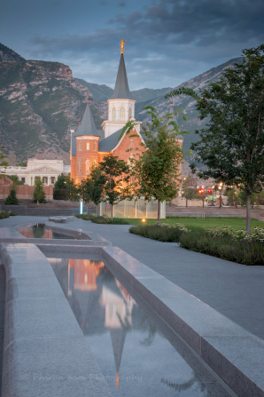 Reflecting pools and trees leading up to the Provo City Center Temple, with mountains in the background.